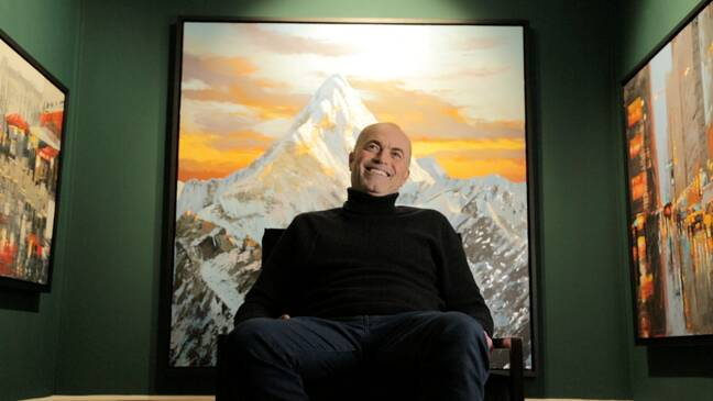 Paul Kenton infront of an original Mountain landscape during his interview at the Mailbox gallery